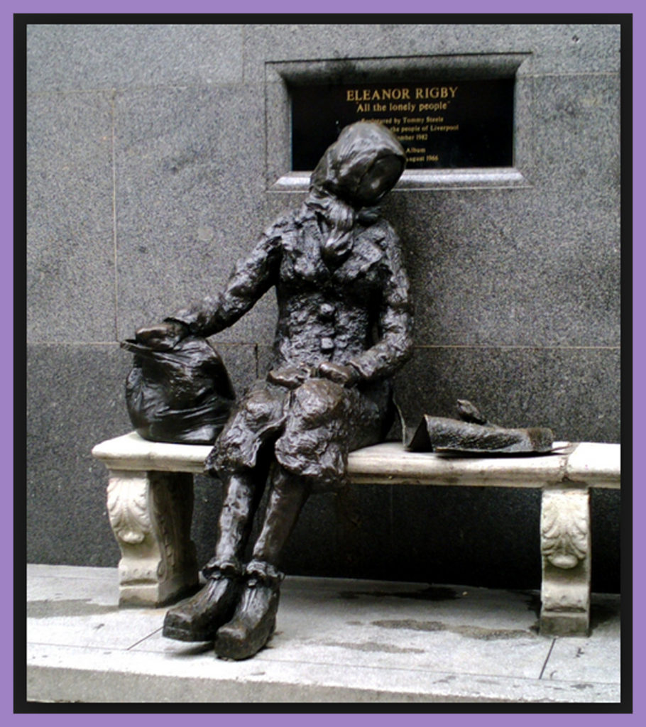 "Statue of Eleanor Rigby in Stanley Street, Liverpool. A plaque to the right describes it as ""Dedicated to All the Lonely People"""