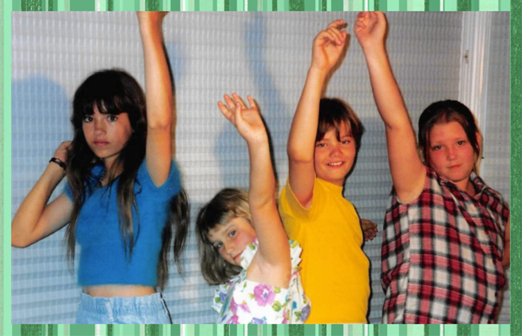 "The cousins love this ""Arm in the Air"" salute; it shows up in a LOT of photos. I still don't know what it means. From left to right Sam, Bree, Alex and Carly."