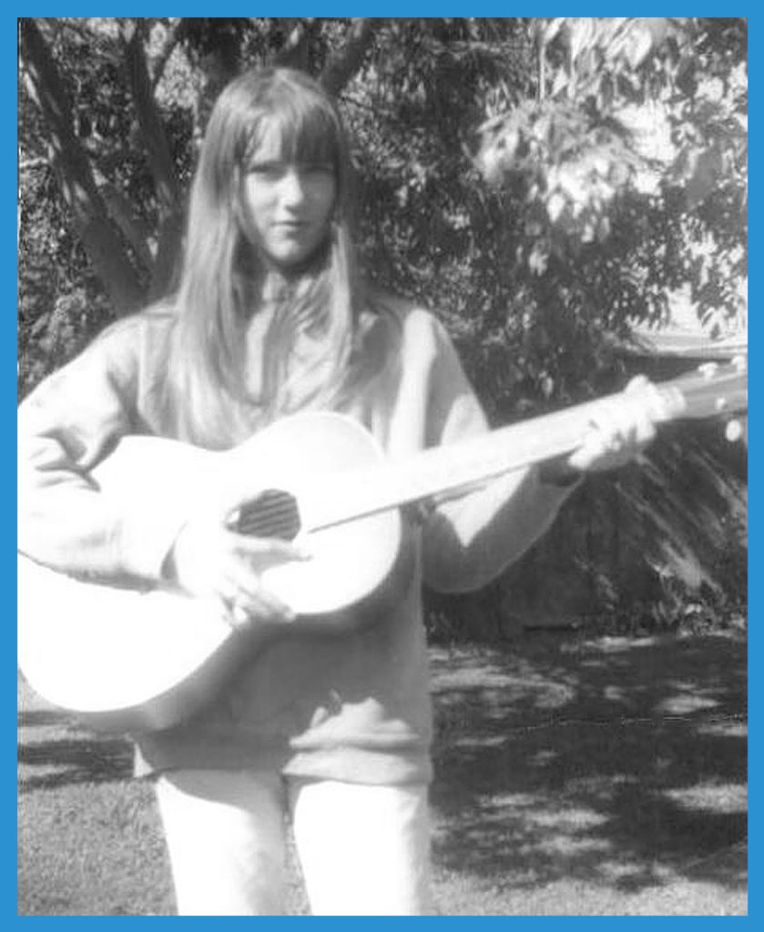 Monkees fan sister Janet with guitar in backyard.