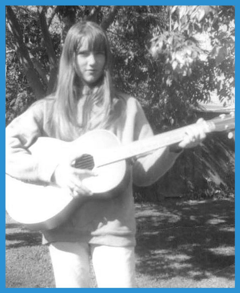 Monkees fan sister Janet with guitar in backyard.