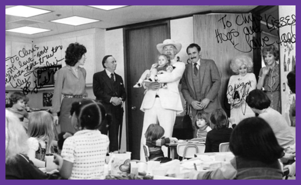 9 to 5 Daycare Scene - Jenny being held, CD to the far left