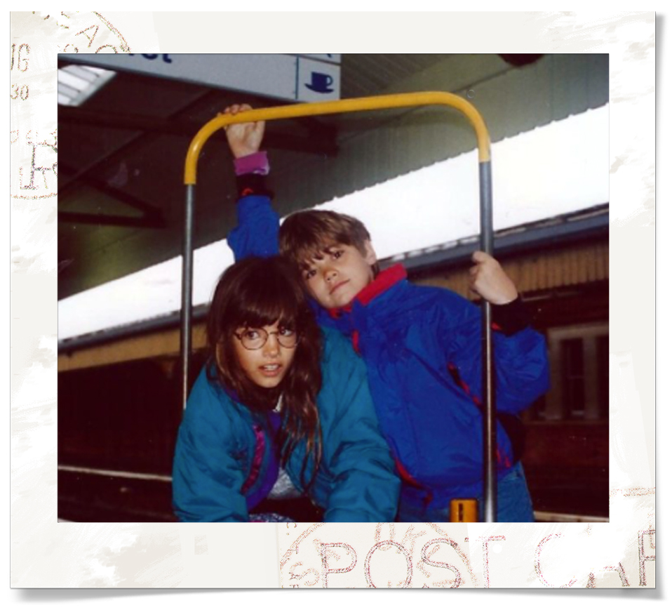 Sam and Alex striking a pose on a baggage transporter at the train station